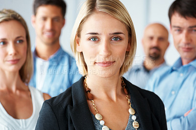 Buy stock photo Portrait of a young businesswoman with her successful business team standing in background