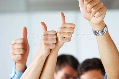 Buy stock photo Business people holding their thumbs up meaning a great business plan