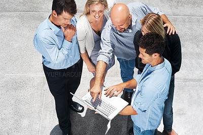 Buy stock photo Top view of happy business executives discussing work on laptop
