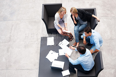 Buy stock photo Top view of a hard working business people sitting together and working on documents