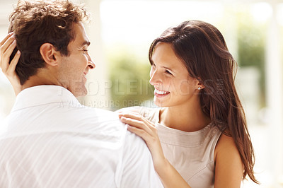 Buy stock photo Portrait of affectionate young couple looking at each other while standing together ouydoors