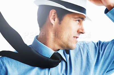 Buy stock photo Handsome business man holding his hat while wind blows his tie