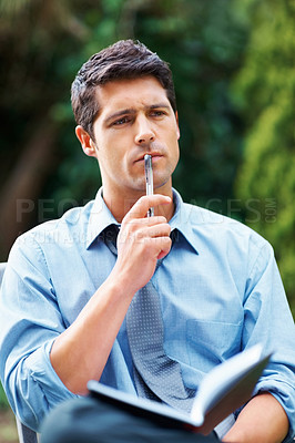 Buy stock photo Business man sitting outdoors with book, looking into distance