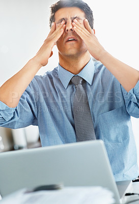Buy stock photo Businessman rubbing his eyes while seated at desk