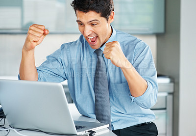 Buy stock photo Businessman holding his fists in excitement while looking at laptop