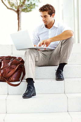 Buy stock photo Relaxed young businessman working on laptop while sittinig outside on some building steps
