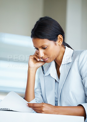 Buy stock photo Pretty business woman sitting at desk while reviewing notes