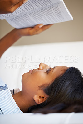 Buy stock photo Pretty woman lying on her back, reading a book