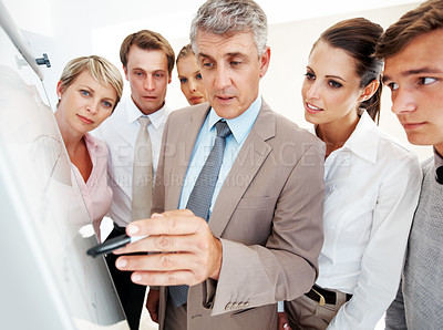 Buy stock photo Senior male executive traning his associates during a meeting at office
