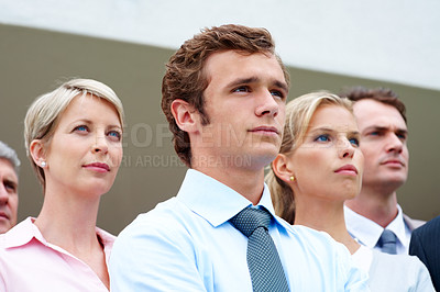 Buy stock photo Confident young male business executive looking away with his coworkers in background
