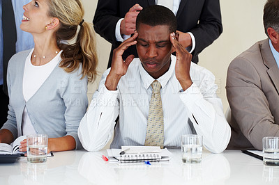 Buy stock photo Young afroamerican businessman suffering from headache during a meeting at office