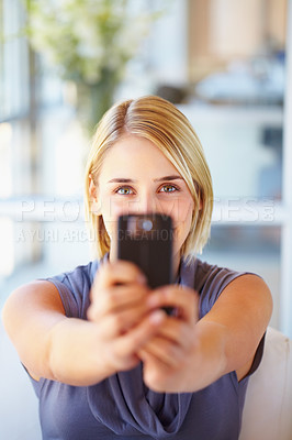 Buy stock photo Pretty young woman taking pictures from her cell phone