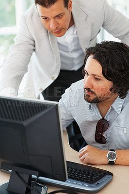 Buy stock photo Two business men working together on computer