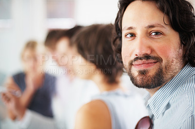 Buy stock photo Focus on young business man with colleagues discussing in background