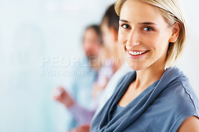 Buy stock photo Young pretty woman smiling with team in blurred background