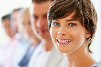 Buy stock photo Focus on pretty woman with colleagues in distance