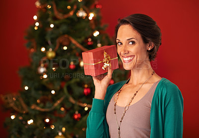 Buy stock photo Shot of an attractive young woman holding her Christmas present