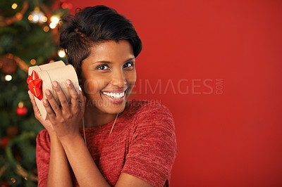 Buy stock photo Portrait of an attractive young woman holding her Christmas gift
