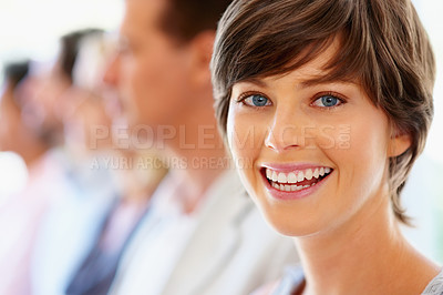 Buy stock photo Focus on pretty woman with team in row in background