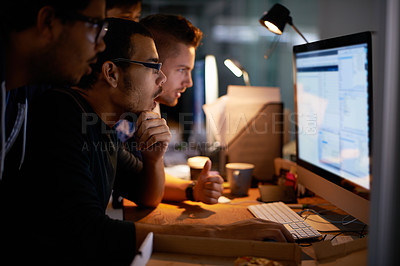 Buy stock photo Cropped shot of a group of young coworkers working in a dimly-lit office