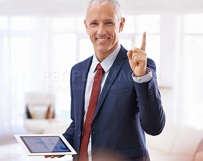 Buy stock photo Cropped shot of a pleased businessman holding a tablet and pointing up