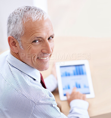 Buy stock photo Shot of a businessman expressing joy at what he has just read on his tablet