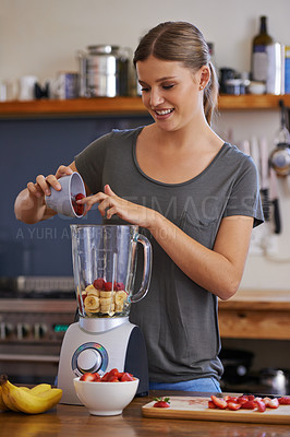 Buy stock photo Shot of an attractive young woman adding fresh fruit to a blender to make a smoothie