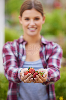 Buy stock photo Cropped shot of a happy young woman holding a handful of fresh strawberries
