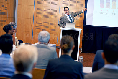Buy stock photo A happy businessman gesturing while giving a presentation at a press conference