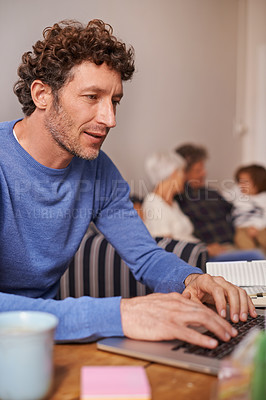 Buy stock photo Shot of a handsome young man using a laptop with his family sitting in the background