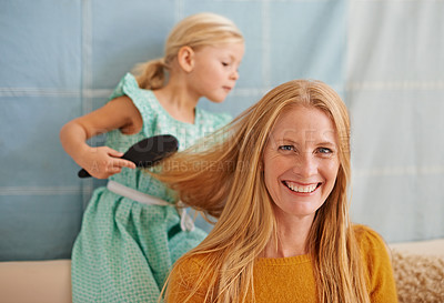 Buy stock photo Shot of a cute little girl brushing her mother's hair