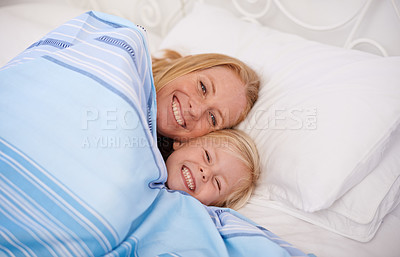Buy stock photo Shot of a mother and her young daughter lying in bed together