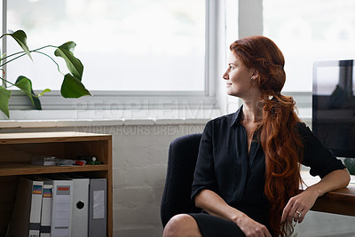 Buy stock photo Shot of a beautiful young businesswoman sitting at her desk and looking out the window