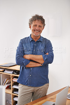 Buy stock photo Portrait of a mature businessman standing with his arms folded behind his desk