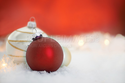 Buy stock photo Two christmas baubles lying on a bed of snow
