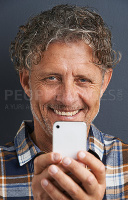 Buy stock photo A cropped portrait of a happy mature man taking a photo with his smart phone