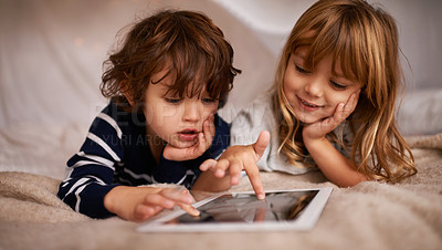 Buy stock photo Shot of two adorable siblings using a digital tablet while lying on a bed