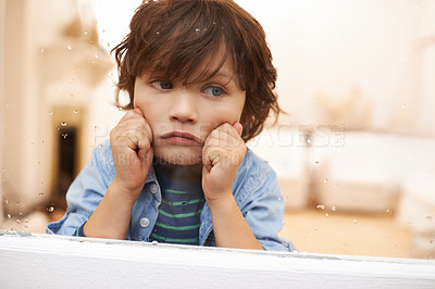 Buy stock photo Shot of an unhappy-looking little boy sitting and looking out a window on a rainy day