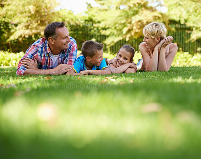 Buy stock photo A front view shot of a happy family lying on the grass outdoors