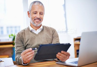 Buy stock photo A happy businessman using a tablet at his desk at work