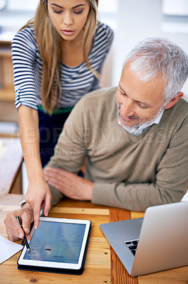 Buy stock photo A beautiful young woman showing her coworker some information on a tablet