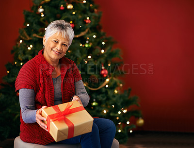 Buy stock photo Cropped shot of a woman in front of a Christmas tree offering a present