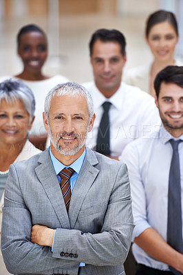 Buy stock photo Portrait of a smiling businessman surrounded by a group of his colleagues