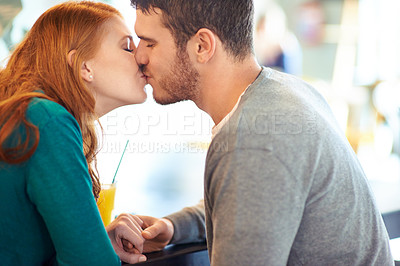 Buy stock photo A cropped shot of a happy young couple kissing while sitting at a cafe
