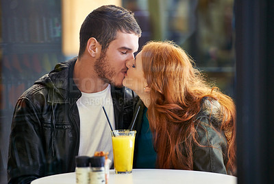 Buy stock photo Cropped shot of a happy young couple kissing while sitting at a cafe