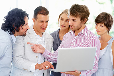 Buy stock photo Group of people discussing something shown on laptop