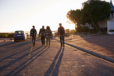 Buy stock photo Rearview shot of a group of friends walking at sunset