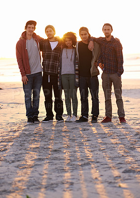 Buy stock photo Shot of a group of friends on a beach at sunset