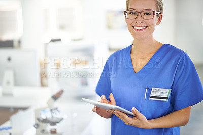 Buy stock photo A beautiful female doctor holding a tablet while standing in a lab