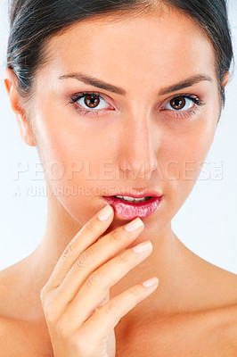 Buy stock photo Shot of a beautiful young woman in studio feeling her soft skin